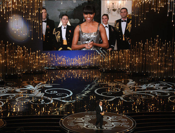 First Lady Michelle Obama, on a video screen via satellite, announces the best picture Oscar with Jack Nicholson, who was at the Dolby Theatre.