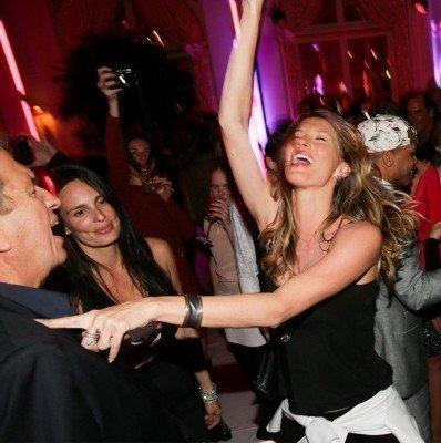 Gisele Bundchen dances while Mario Testino laughs at a party celebrating the opening of his exhibition at the Prism Gallery in Los Angeles.