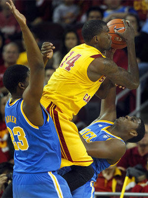 Trojans forward Dewayne Dedmon elevates between Bruins forwards Tony Parker and Jordan Adams for a shot in the second half Sunday.