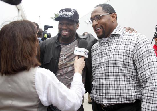 Ray Lewis and rapper 50 Cent talk to a reporter before the start of the Daytona 500.