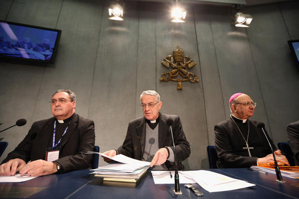 Father Federico Lombardi, center, director of the Holy See Press Office, along with Archbishop Pier Luigi Celata, right, hold a news conference at the Vatican to discuss changes to Roman Catholic Church law that will enable cardinals to select Pope Benedict XVI's successor sooner.