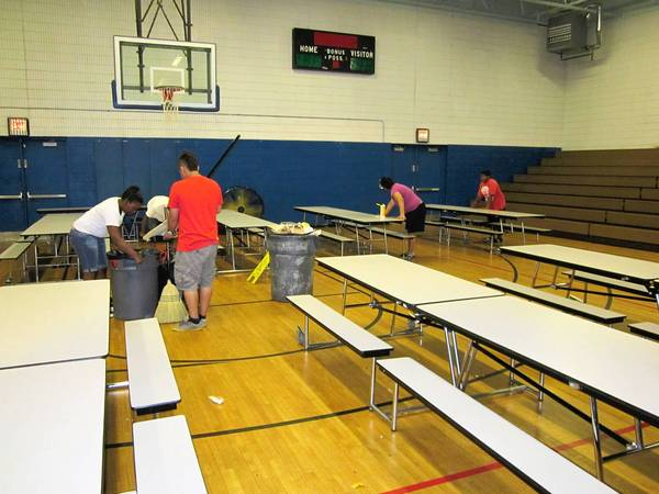 Members of Lake County's youth summer employment program clean up Waukegan High School Brookside Campus.