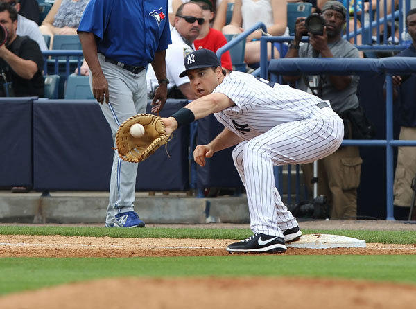 New York Yankees first baseman Mark Teixeira (25) catches the ball at first base in the fifth inning against the Toronto Blue Jays during spring training at George M. Steinbrenner Field.