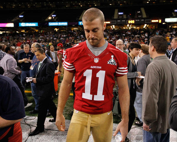 San Francisco 49ers quarterback Alex Smith walks on the field after he was not given a booth to answers question from journalists during Media Day for the NFL's Super Bowl XLVII in New Orleans, Louisiana January 29, 2013.