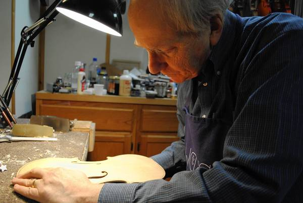 Gerry Field, of Field Violin Workshop, 451 Roger Williams Ave., carves an f-hole in a top of a violin he is building on Feb. 21, 2013.