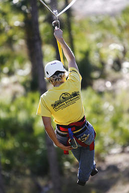 One of the guides Miranda Watford of Florida Eco-Safaris goes down a zipline at tree top heights, St. Cloud.