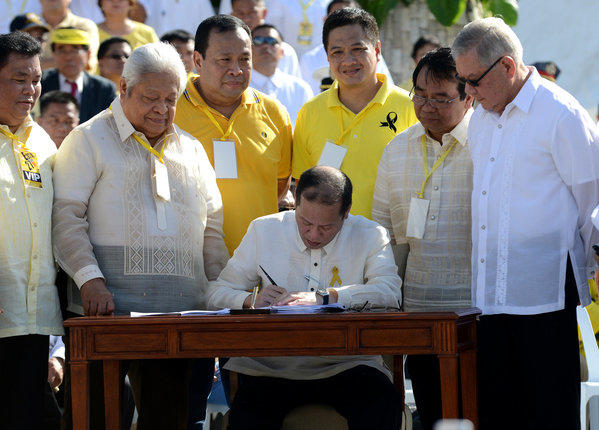 Philippines President Benigno Aquino III signs a bill Monday during ceremonies marking the 27th anniversary of its uprising against Ferdinand Marcos.