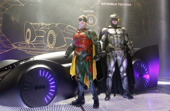 Batman and Robin pose in front of the Batmobil during the 'Batman Live Show' photocall at O2 World on January 11, 2012 in Berlin, Germany.