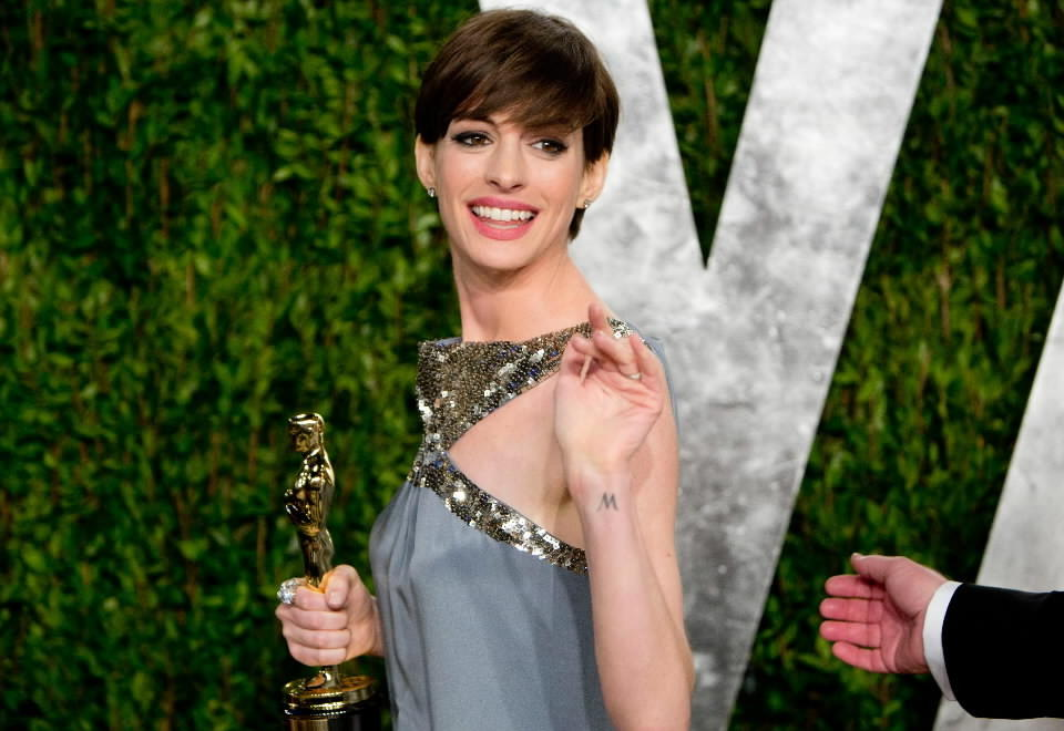 Anne Hathaway carries her Oscar for best supporting actress on Sunday night.