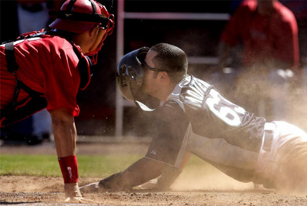 Angels catcher Hank Conger tags out Mariners' Jesus Montero at home plate.
