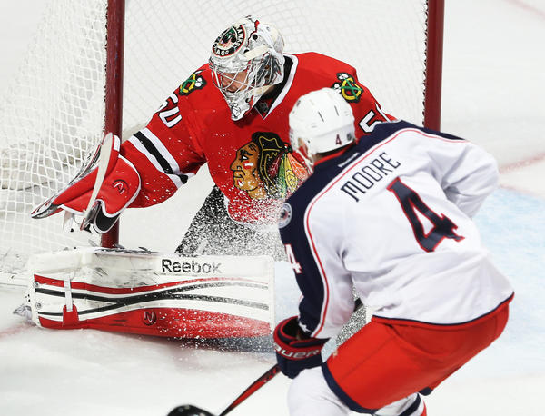 Chicago Blackhawks goalie Corey Crawford (50) deflects a shot by Columbus Blue Jackets defenseman John Moore (4), during the second period of their game at the United Center, in Chicago, on Sunday February 24, 2013.     (Nuccio DiNuzzo/Chicago Tribune)  B582695842Z.1 ....OUTSIDE TRIBUNE CO.- NO MAGS,  NO SALES, NO INTERNET, NO TV, CHICAGO OUT, NO DIGITAL MANIPULATION...