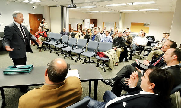 Dane Bauer, left, speaks to members of the Sora Development group, who were gathered for a meeting with EDC and others at the Washington County Commissioners conference room on Monday.