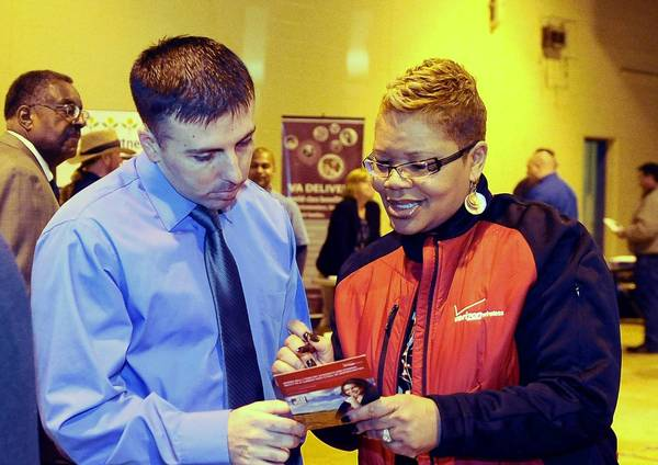 Sgt. Jason Lefebvre, left, of Damascus, who is in the Maryland National Guard, talks with Teresa Williams, a human resources recruiter for Verizon, at a jobs fair for veterans which was held at the Ruhl National Guard Armory.