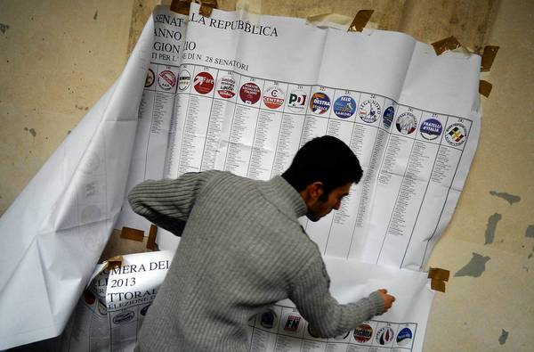 A worker takes down an electoral information banner at a polling station in downtown Rome.