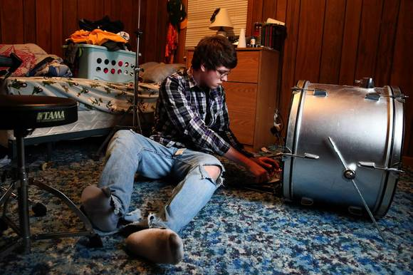 Seth Melvin, 15, arranges a drum kit in his room Thursday afternoon. The teen is scheduled to get part of his right leg amputated in March.