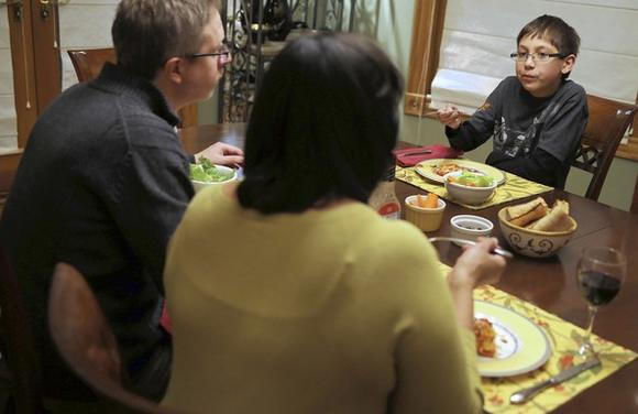 Francisco Steib, 10, discusses his school day with his parents, Kurt and Maggi, over dinner.