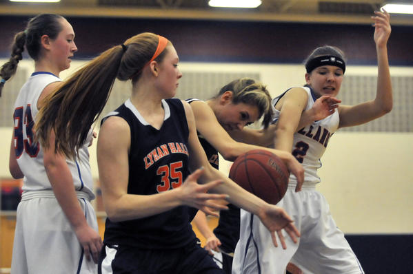 Kim Petit and Hayley Hergott of Lyman Hall fight Sammie Olson for a rebound during Tolland's 47-41 victory Monday.