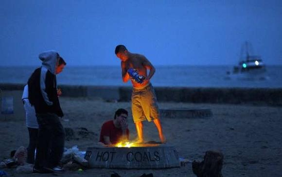 Friends huddle around a fire ring at Corona del Mar State Beach.