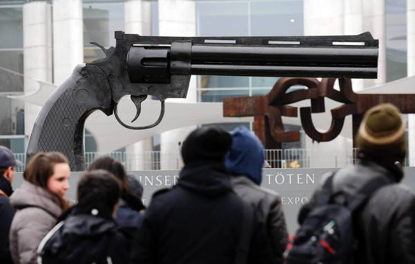 "People watch a sculpture showing a pistol, inspired by Swedish artist Carl Frederik Reutersvaerd sculpture's ""Non-Violence"", in front of the Chancellery in Berlin. The German peace initiative ""Aktion Aufschrei - Stoppt den Waffenhandel"" (Outcry - Stop the arms trade) protests with the sculpture on a square in front of the Chancellery against the German arms trade."