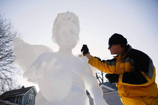 Fran Volz touches up a 7-foot snow angel in his backyard in Elgin, Illinois. After almost every snow fall, Volz sculpts something new for his community to enjoy.