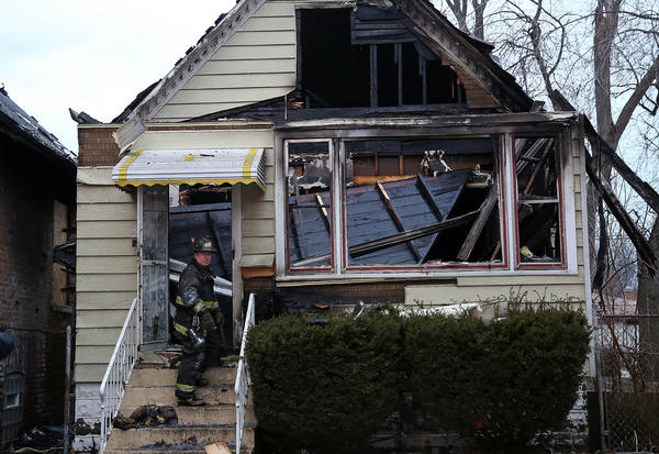 A firefighter stands on the front steps of a house on the 8800 block of South Parnell Avenue.