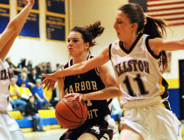 Harbor Lights Shelby Donovan (left) drives the lane against Pellstons Ainsley MacLean (right) during a Class D district contest Monday at the Alanson High School gym.