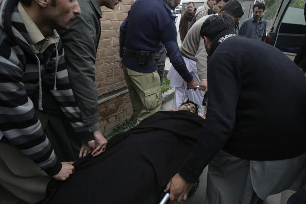People carry the body of a police officer into an ambulance in Mardan. Pakistan, on Tuesday. Police say gunmen shot the officer while he was protecting a team of polio workers during a U.N.-backed vaccination campaign in northwestern Pakistan.