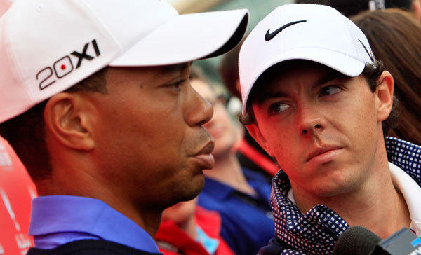 Rory McIlroy of Northern Ireland (R) looks at Tiger Woods of the U.S. during an interview ahead of the Abu Dhabi Golf Championships January 15, 2013.