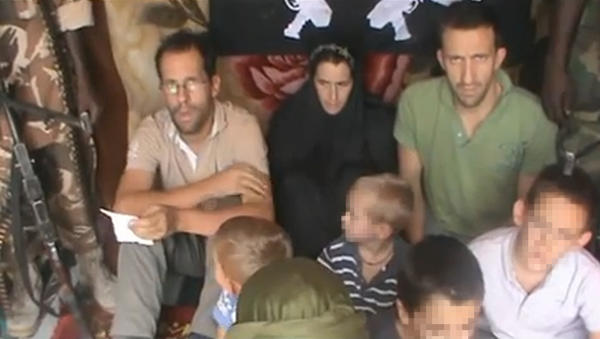 A picture taken from a YouTube video shows Tanguy Moulin-Fournier, left, sitting next to his wife, Albane (wearing a black veil), their four children and his brother Cyril, along with an armed man.