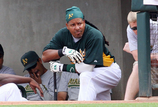 Oakland Athletics' Manny Ramirez watches from the dugout during their spring training game against the Los Angeles Angels at Phoenix Municipal Stadium in Phoenix, Arizona, March 5, 2012.