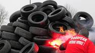 A Goodyear worker uses a red flare to burn 1,173 tyres symbolizing 1,173 employees next to the Goodyear tyres factory in Amiens