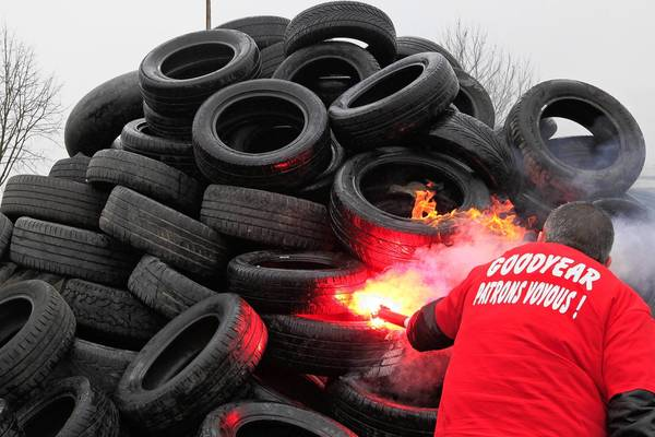 A Goodyear worker uses a red flare to set fire to 1,173 tires symbolizing the 1,173 employees next to the Goodyear tire factory in Amiens, France. U.S. tire maker Goodyear confirms a project to close the plant, which, if undertaken, would lead to the layoff of 1,173 jobs. In a company statement Goodyear stated that the plant closure is the only possible option after five years of unsuccessful negotiations.