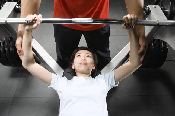 Male instructor training woman with bar bells in gym, high angle view .