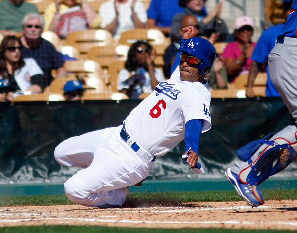 Los Angeles Dodgers third baseman Jerry Hairston Jr. (6) scores in the first inning against the Chicago Cubs during a spring training game at Camelback Ranch.