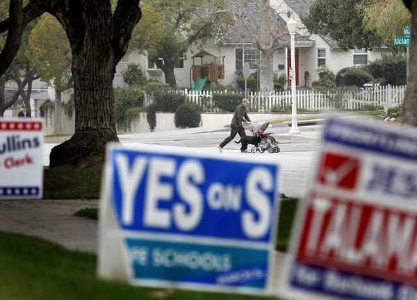 A walker is seen in the background of election signs in the 1500 block of 6th St. in Burbank.