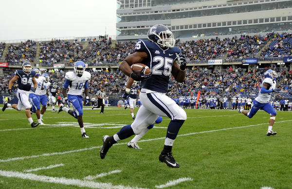 Connecticut running back Martin Hyppolite (25)races down the sideline for a touchdown against Buffalo.