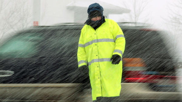 A Schaumburg police officer directs traffic outside of Portillos along Golf Road in Schaumburg on a snowy Tuesday.