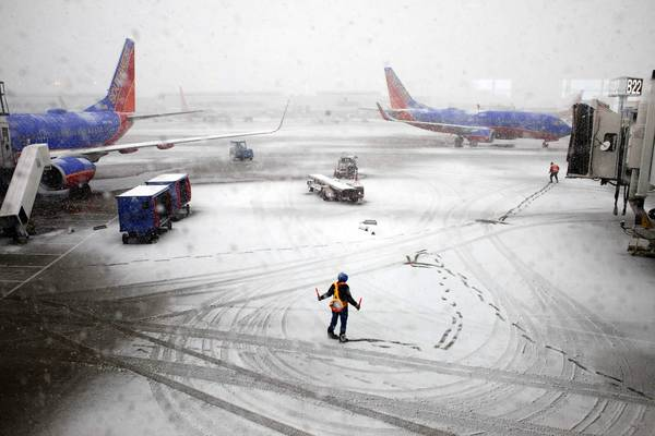 Southwest Airlines employees guide an arrving flight to the gate at Midway International Airport in Chicago. Several flights were canceled or delayed due to the winter storm.