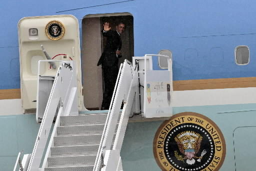 President Obama waves as he boards Air Force One to depart Lang