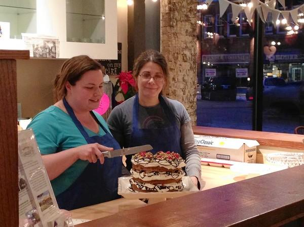 Nina Cater prepares to cut into a cake at Sugar Path, the dessert shop she opened in December with her sister, Michelle Adams, right.