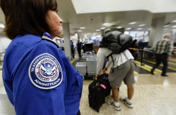 A TSA security officer watches as passengers go through security in Salt Lake City, Utah. Travelers can expect longer security lines as the automatic spending cuts would force the TSA to furlough - temporarily lay-off - screening agents.