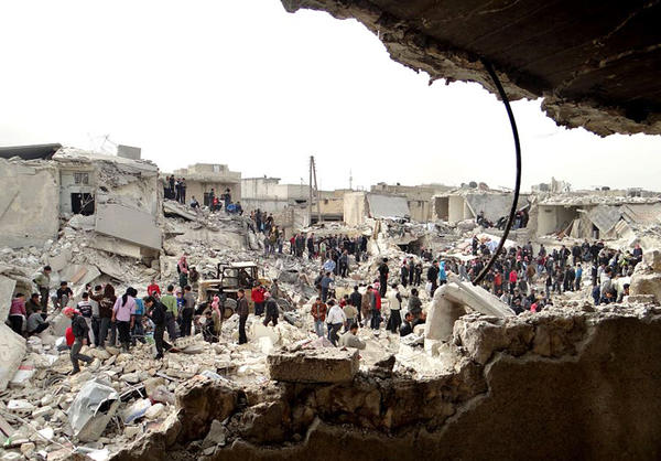 A citizen journalism image provided by Aleppo Media Center, which has been authenticated based on its contents and other AP reporting, shows people searching the rubble Tuesday for dead bodies and injured victims at a site where houses were hit by a government missile attack.