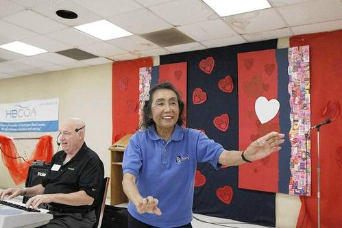 Helen Tangcay, right, performs a Hawaiian dance to the sounds of Don Gay on the keyboard at the Rodgers Seniors' Center. The roof leaks over the stage and throughout the facility.