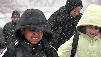 Students from Coleman Elementary School brave the snow and cold to cross Liberty Street in Elgin, Ill.