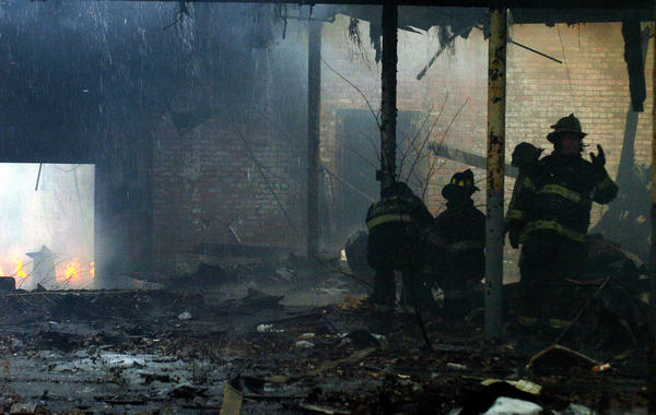 Firefighters work at the scene of a warehouse fire in Chicago Heights, Ill. Medics stood by to take care of any needed assistance at the nearby Golden Towers Senior City, where smoke had entered the building. The smoke affected some residents of the senior center and also interrupted voting at a polling place set up inside.