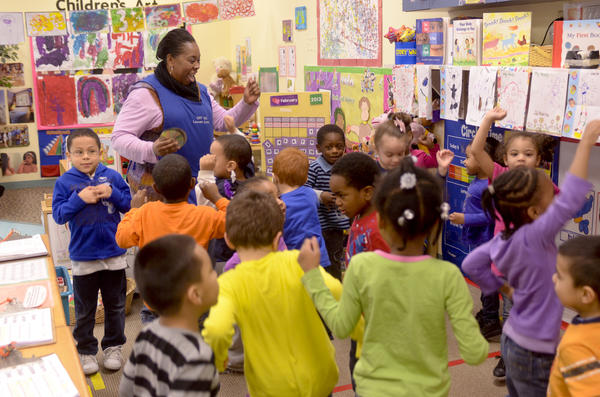 Preschool teacher Marilyn Gooch dances with her class on Tuesday morning at CRT's Locust Street Early Care & Education Center.