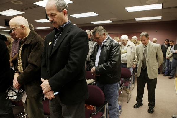 At a meeting of the Rapid City Council this month, attendees bow their heads in prayer.