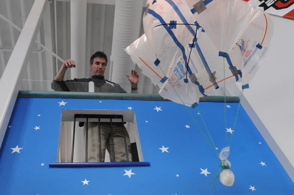 General Electric's Dan Reynolds drops an egg connected to a parachute as part of the egg drop experiment as Imagine Nation Museum in Bristol celebrated National Engineers Day Friday.