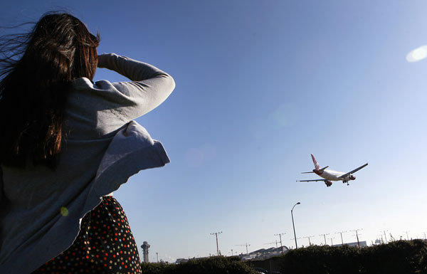 A woman watches a plane come in for a landing on the north runway at Los Angeles International Airport.