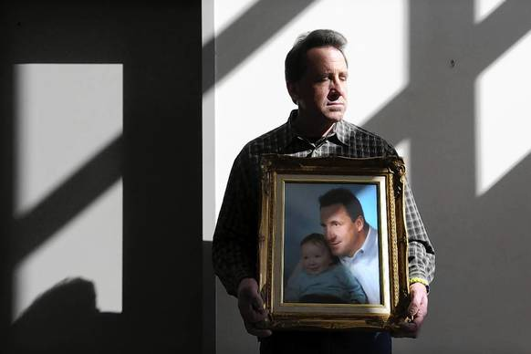 Neil Heslin holds a 2006 photograph of himself and his son, Jesse Lewis, who was killed in the Sandy Hook massacre.